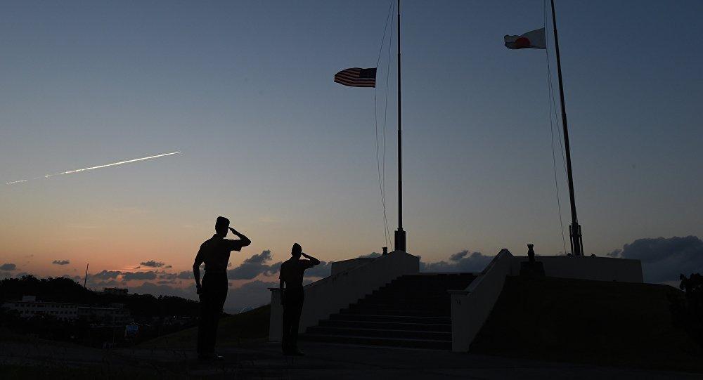 Militares da Marinha dos EUA durante a cerimônia de descida da bandeiras norte-americana e japonesa em Camp Forester, perto da base militar de Futenma em Ginowan, na prefeitura de Okinawa, em 14 de novembro de 2014