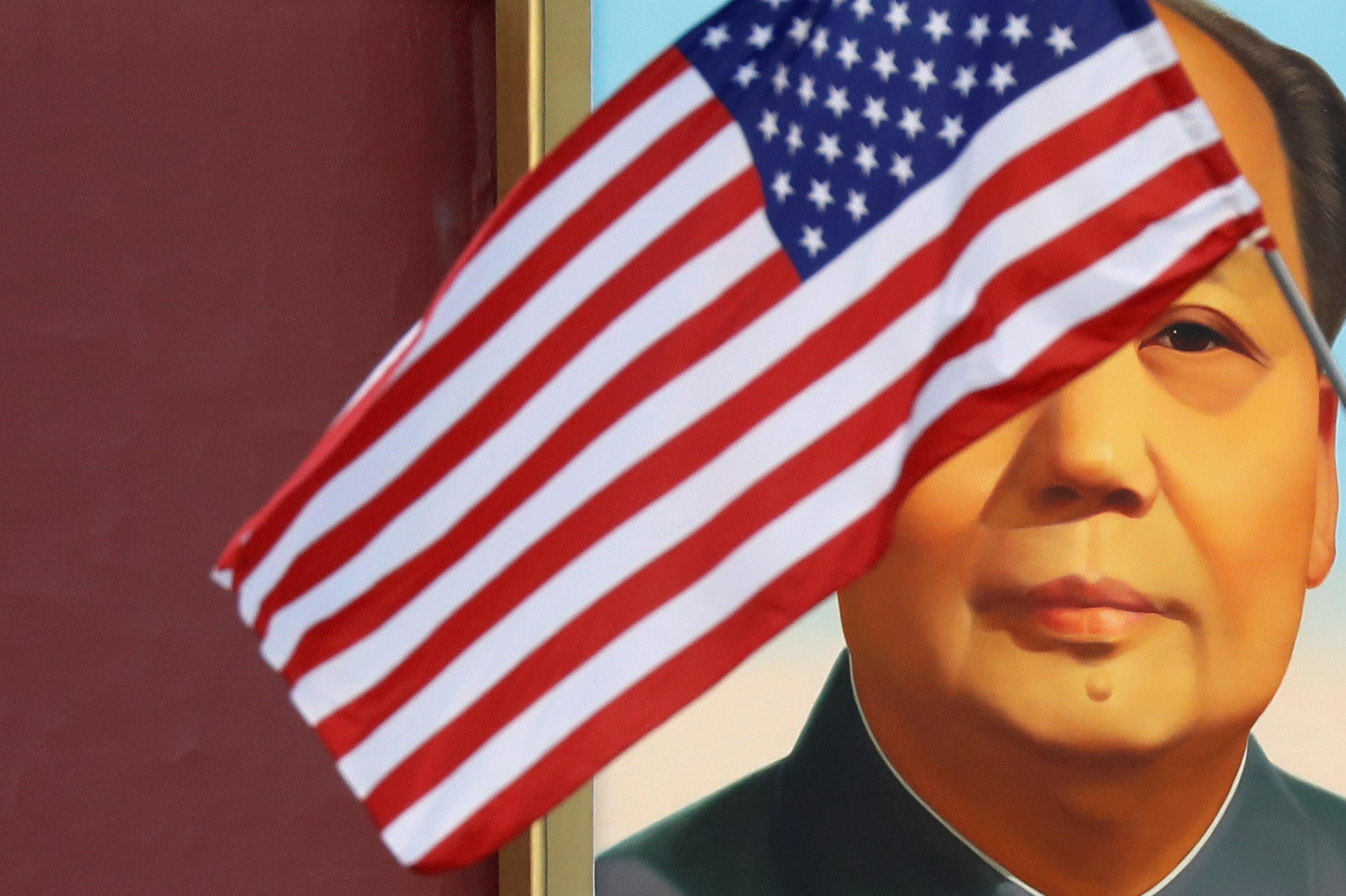 Uma bandeira dos EUA flutua em frente a um retrato do ex-presidente chinês, Mao Tsé-Tung, no portão da Praça da Paz Celestial durante a visita do presidente dos EUA, Donald Trump a Pequim, 8 de novembro de 2017.
