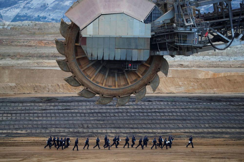 Unidades especiais da polícia alemã correm diante de uma escavadeira durante uma manifestação contra extração de carvão na mina de Garzweiler, nordeste de Colônia, Alemanha