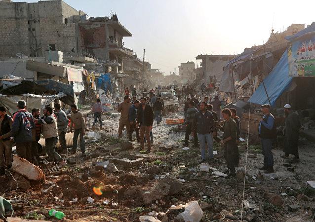 Sírios observam destroços provocados por ataque aéreo em Atareb, na província de Aleppo