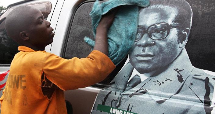 Jovem lavando veículo com a imagem do presidente do Zimbábue, Robert Mugabe, Harare. Zimbábue, novembro 15, 2017