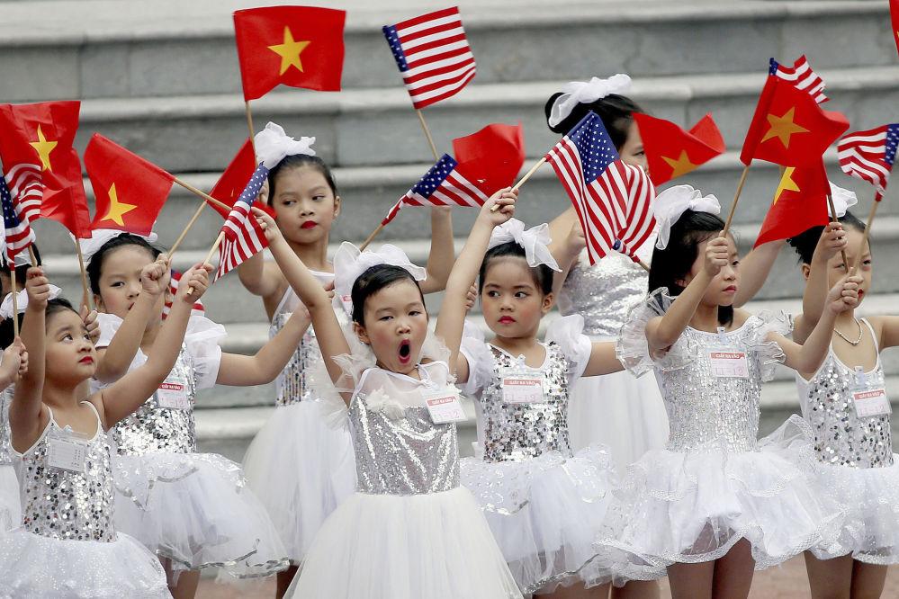 Crianças vietnamitas antes da cerimônia de saudação do presidente norte-americano, Donald Trump