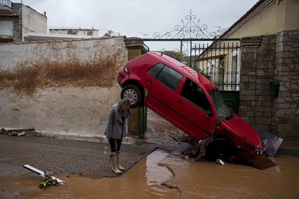 Mulher perto de carro levado por inundação em Atenas, Grécia