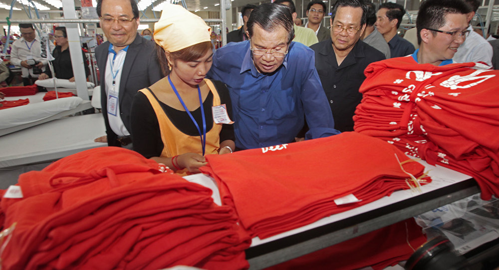 Cambodian Prime Minister Hun Sen, center, leans over a garment worker