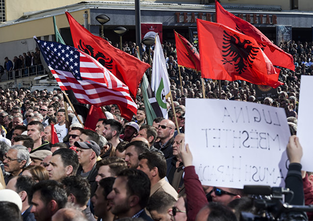 Albaneses em Kosovo com bandeiras da Albânia e dos EUA