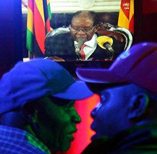 Pessoas assistem na televisão o presidente zimbabuano Robert Mugabe se dirigindo à nação em um bar em Harare, Zimbábue, 19 de novembro de 2017