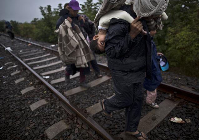 Migrantes sírios andando nos trilhos com crianças nas costas