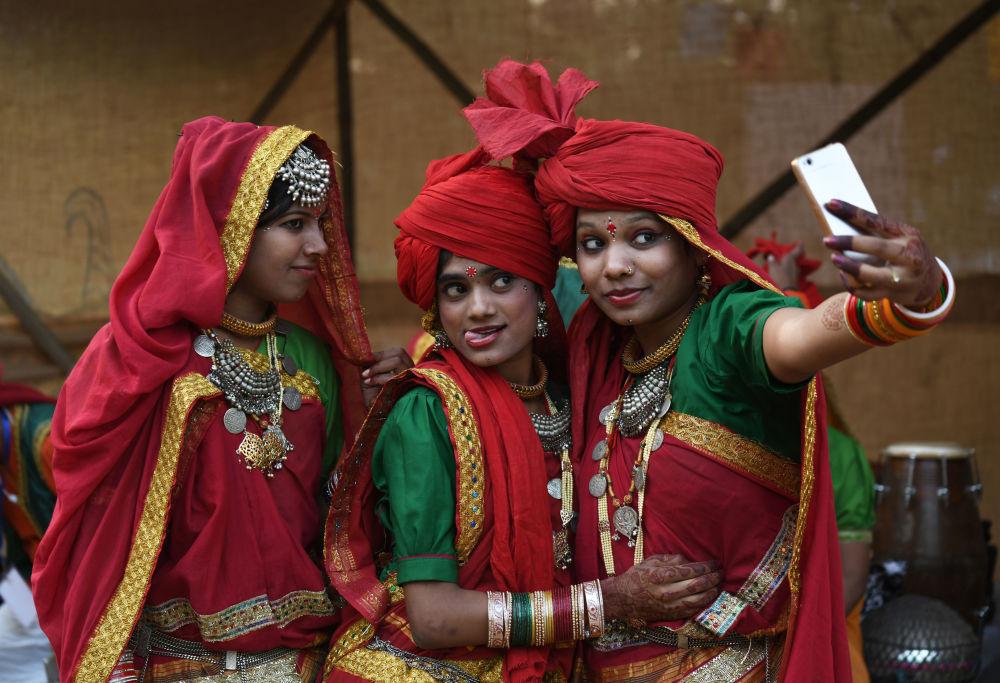 Artistas hindus tiram selfie antes do show dedicado a evento cultural