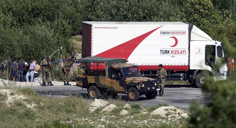 Funcionários do Crescente Vermelho e militares turcos distribuem comida para migrantes sírios na vila de Guvecci, província de Hatay, Turquia (arquivo)